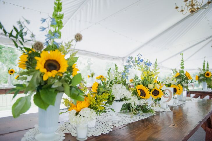 Caitlin and Sean decorated each family-style wooden table with a personal touch. Tablescapes of sunflowers, greenery, white hydrangeas and blue lilies of the valley from Mark Bryan Designs were placed in antique, heirloom or borrowed white vases as antique lace was used as a runner.