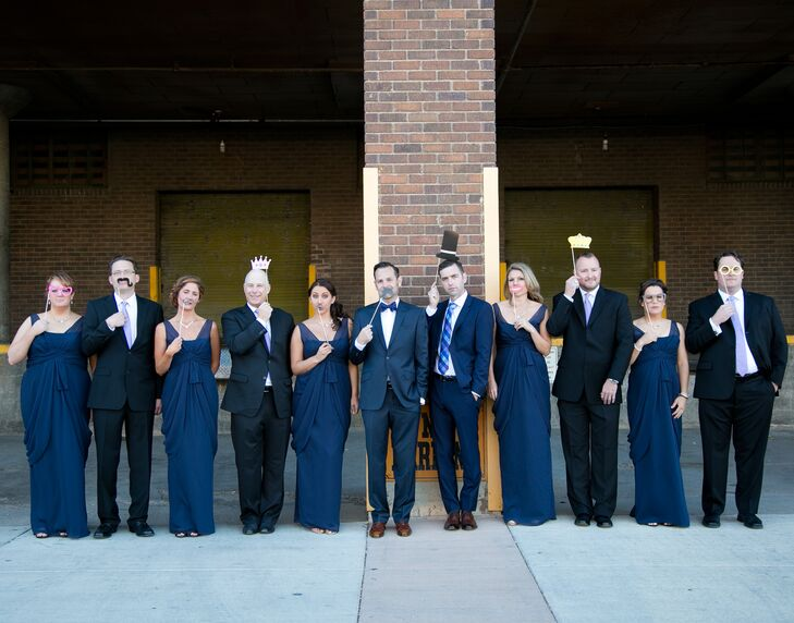 The groomsmen wore black suits, while the grooms wore navy blue to match the groomsmaid dresses. The women wore matching full-length, sleeveless gowns by Vera Wang accessorized with Givenchy jewelry.