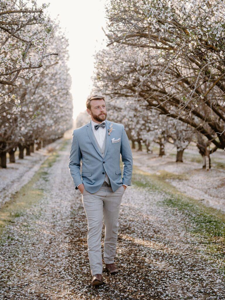 Groom wearing light blue suit at outdoor celestial wedding