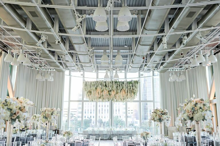 All-white reception decor with white floral chandelier