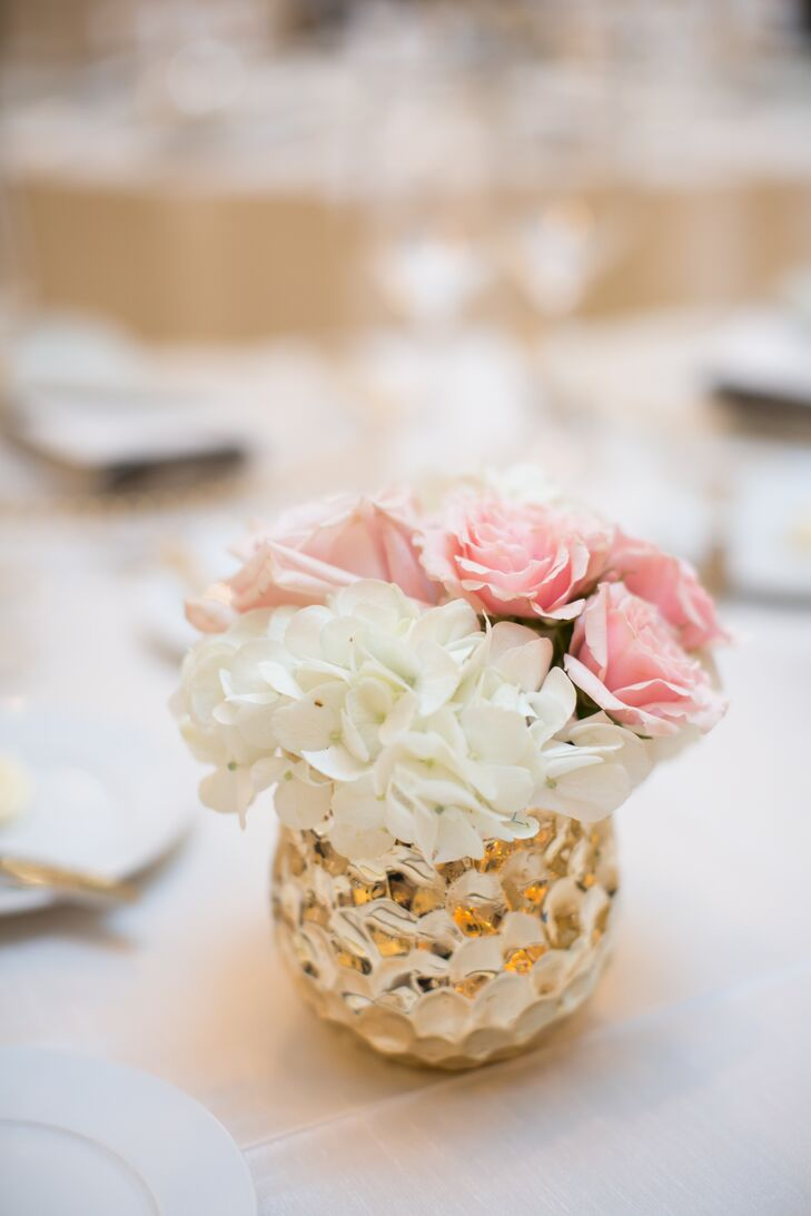 Neutral linens and metallic votives topped each round reception table along with Lucite candelabras, bejeweled globes and centerpieces that incorporated white hydrangeas and pink roses.