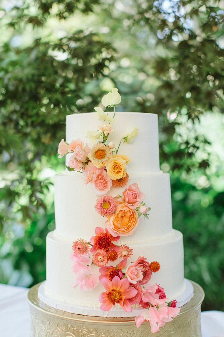 Three-tier cake with ombre cascade of fresh flowers.