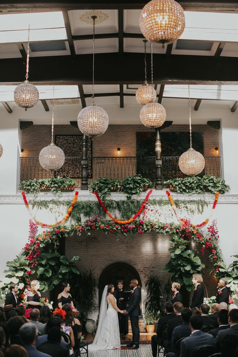 Glass orb chandeliers hanging about wedding ceremony