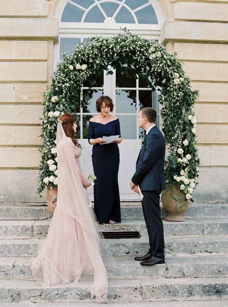 The ceremony took place outdoors, on the back steps of Chateau de Courtomer in Courtomer, France. Liv and Jesse exchanged vows under a lush arch of white garden roses, eucalyptus and greenery displayed in two stone urns.