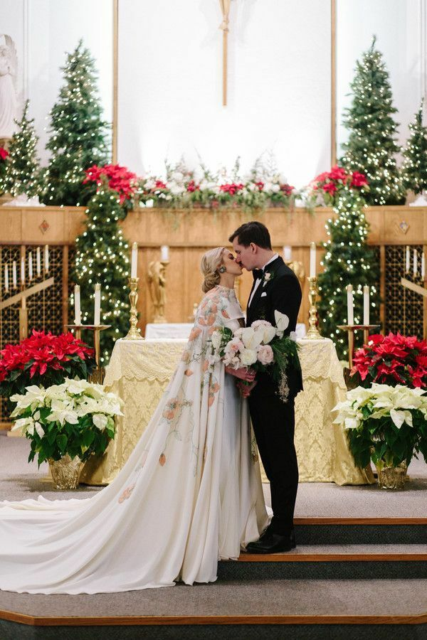Couple sharing kiss in church surrounded by poinsettias