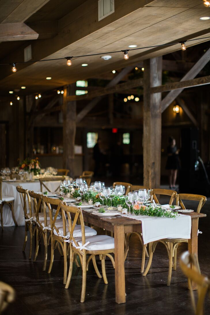 For the reception at Winvian Farm in Morris, Connecticut, Arianne and Adam paid tribute to the striking scenery and the venue's innate charm, topping the rustic farm tables' Swiss-dot linens with eye-catching arrangements of bright roses, dahlias, stock and hypericum. Bistro lights and chandeliers dripping with Southern smilax instilled the expansive space with a sense of romance and ambiance.