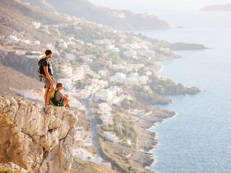 Couple hiking a cliff on honeymoon