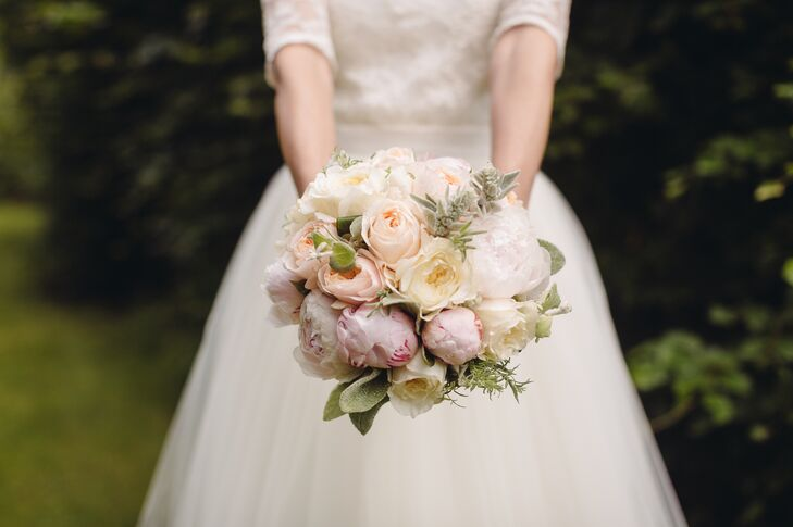 Linda carried a bouquet with blush and ivory peonies, antique pink roses and dusty miller. Its pastel colors perfectly went with her ivory wedding dress.