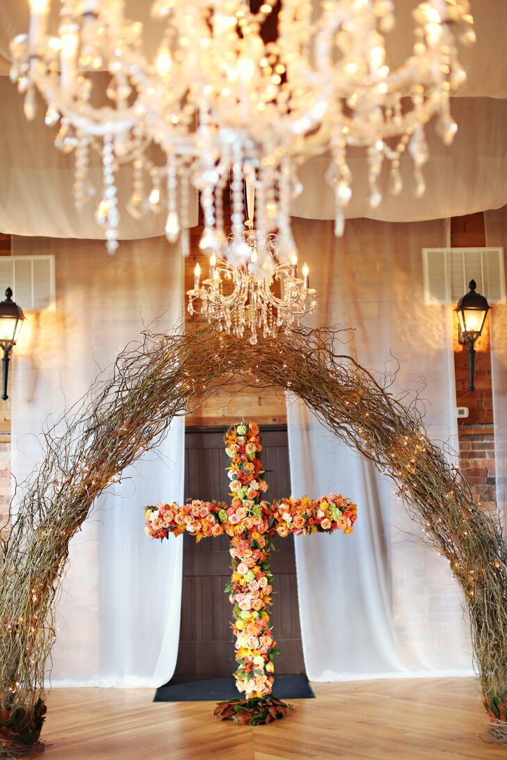 Two ceremony arches were created using curly willow vine and white twinkle lights with a six foot free standing wooden cross covered in orange flowers as the backdrop.