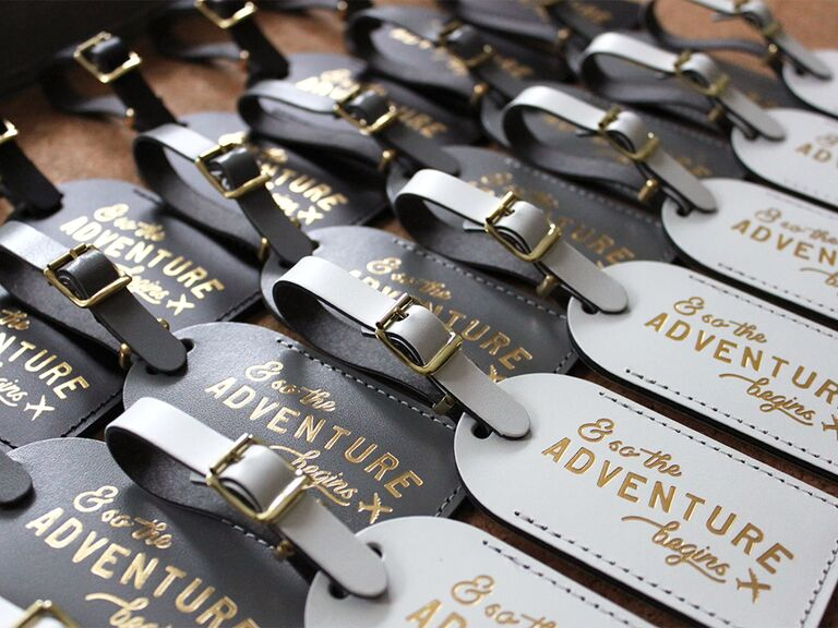 Dark and light gray luggage tags with gold text and small airplane graphic