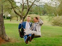 grooms on swing at rustic outdoor Vermont wedding