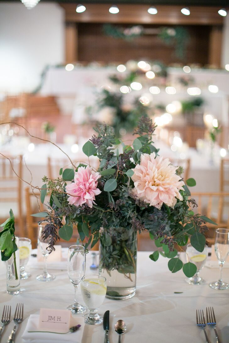 Each table was set with a combination of blush and cream dahlias and copious amounts of greenery, helping to maintain an intimate, rustic feel in a spacious indoor space.