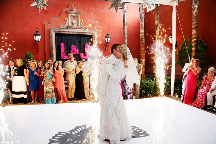 Louisa and Joseph shared their first dance on a white dance floor surrounded by fireworks. It was romantic and striking—just what they wanted.