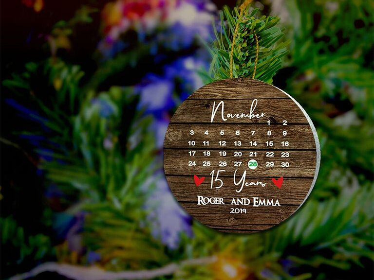 Wood background circle ornament with calendar design and heart around wedding date