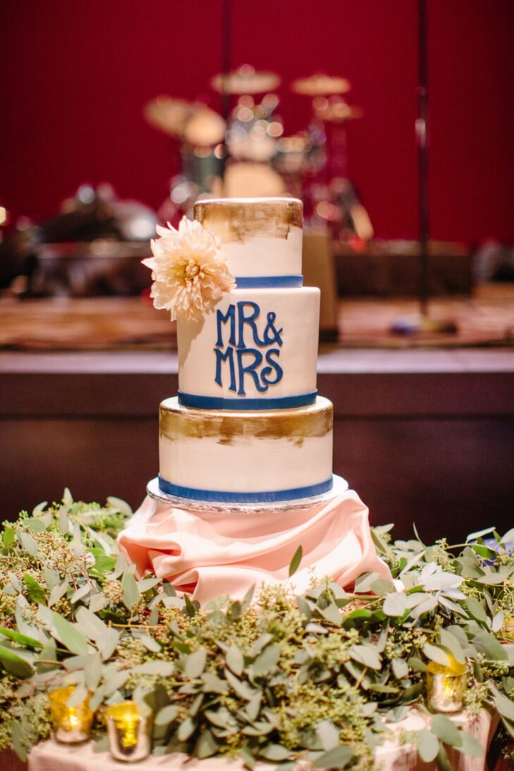 Millie and Luke offered their guests three cakes, including a standard four-tier white iced wedding cake with gold and bright blue details. The bride and groom's cakes were displayed on opposite sides; Luke had a TCU football stadium cake, and Millie had a UK basketball stadium cake.