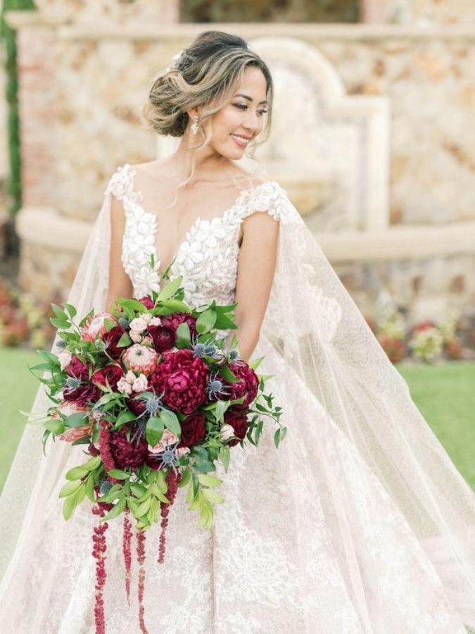 Bride holding cascading burgundy bouquet