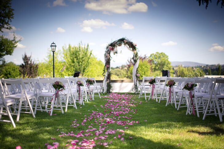 The ceremony took place outdoors on the lawn at Villa Tolomei Hotel in Florence, Italy. The ceremony aisle was lined with pink roses, and at the end of the altar stood a wedding arch covered in greens and pink flowers for the altar area.