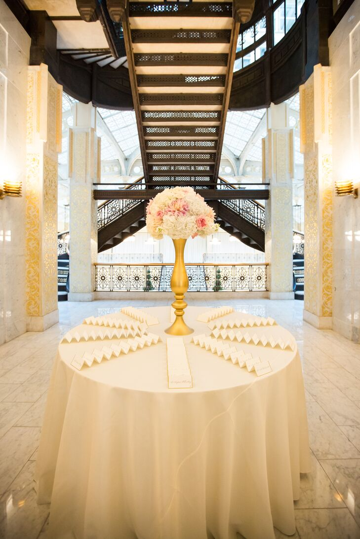 Guests found their seats at a simple escort card display that incorporated gilded cards and a lush arrangement of blush and white blooms.