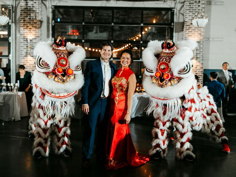 Bride and groom with cultural Chinese lion dancers at wedding reception