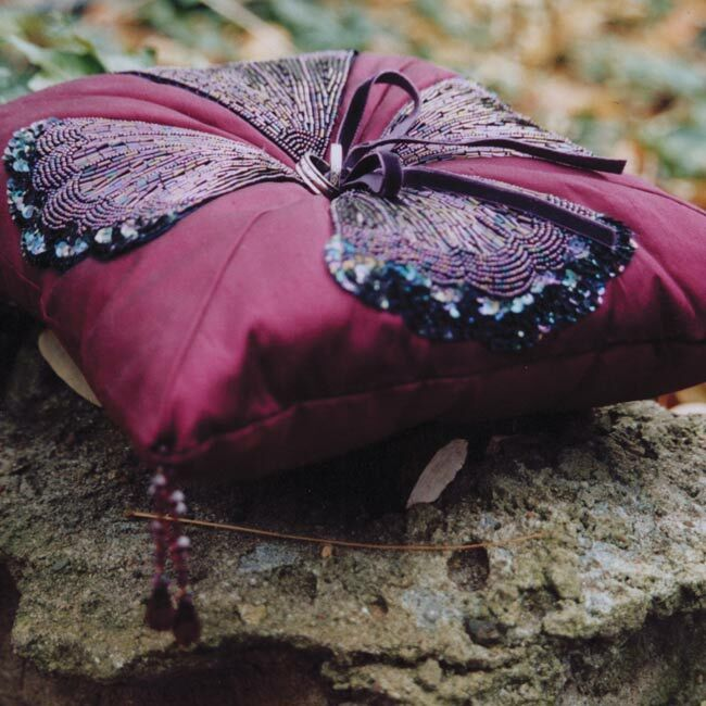 Elizabeth used plum-colored raw silk, beaded appliques, and crystal tassels to create a one-of-a-kind ring bearer pillow. Velvet ribbon sewn in the center secured the rings in place.