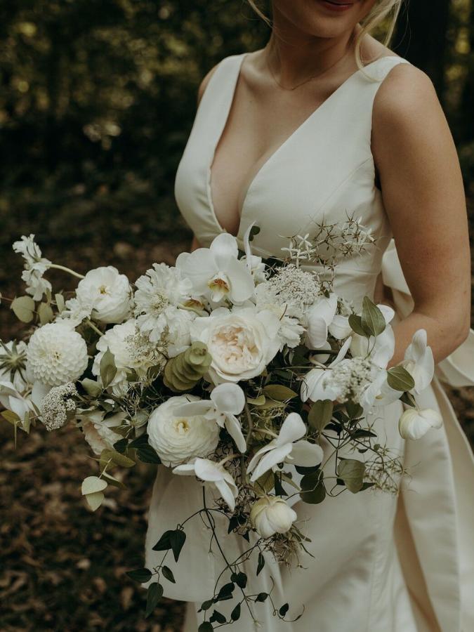 Bride holding boho white wedding bouquet