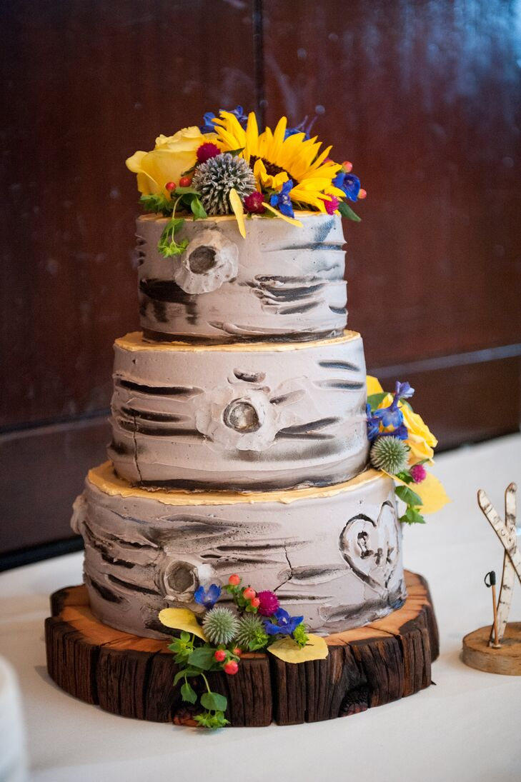 """Kimberly and Charles enjoyed a three-tier wedding cake from Whole Foods in Colorado Springs. """"We chose one of their most popular kinds—the berry chantilly whipped vanilla buttercream cake,"""" Kimberly says. """"As for its design, we chose a custom-made Aspen tree with our initials carved into a heart on the side."""""""