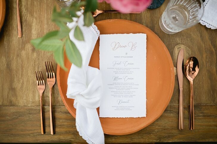 Elegant Place Setting with Orange Dinnerware, Gold Flatware and Menu