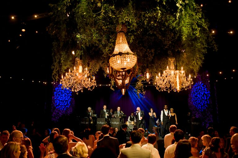 Crystal chandeliers over live band while guests dance at wedding reception