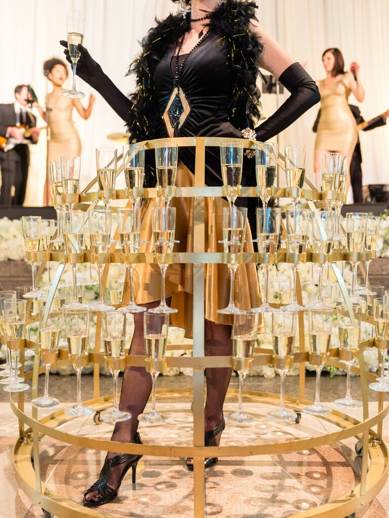 Champagne server at wedding reception with metal skirt holding champagne glasses