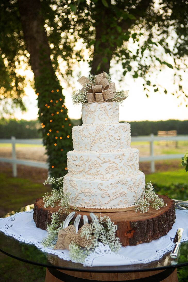 """""""Our cake was delicately decorated with baby's breath and burlap, and positioned on a real tree slab with horseshoes strategically arranged,"""" says Erin. """"I must say, was the most beautiful cake I'd ever seen!"""""""