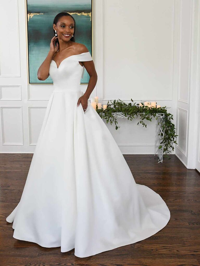 essense of australia white a line wedding dress with sweetheart neckline pockets off the shoulder sleeves and pleated ball gown skirt
