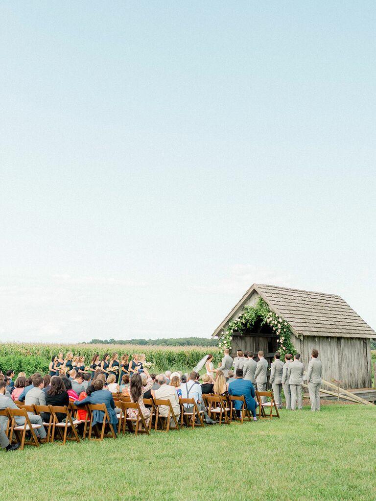 Guests at outdoor daytime casual wedding at barn