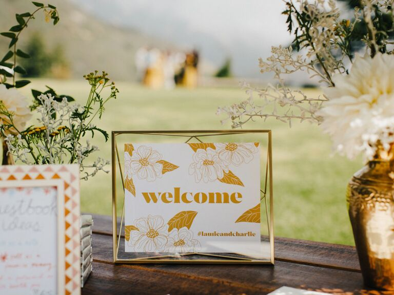 Framed gold wedding hashtag sign on top of bar
