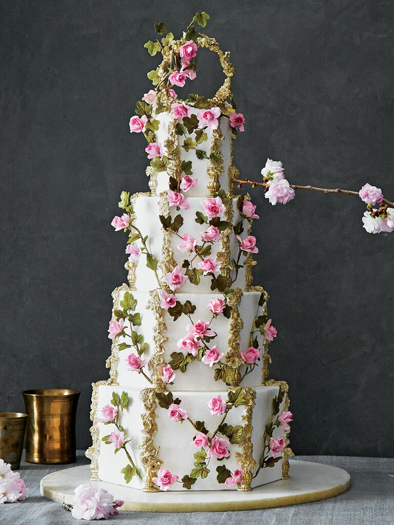 Ornate four-tier wedding cake with pink flowers