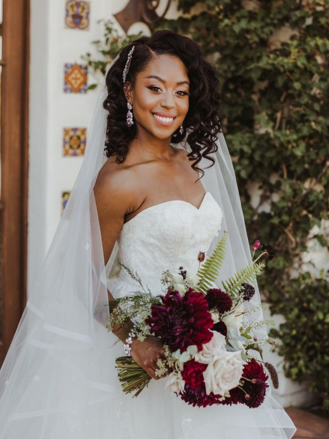 Bride wearing veil and holding burgundy bouquet