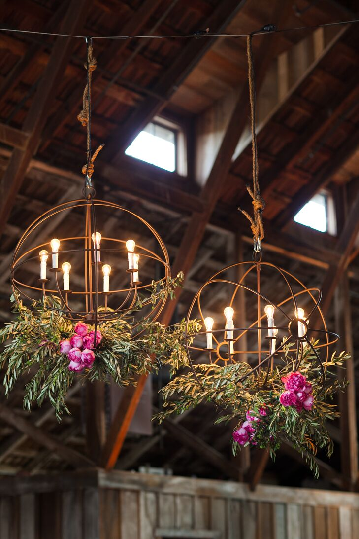 Two large iron orbs, draped in flowers and lit from above, hung over the dance floor at the center of the barn.
