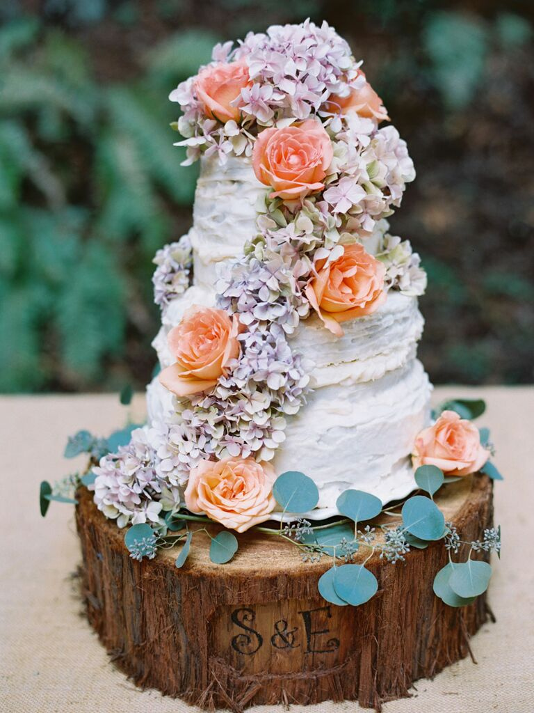 Three-tier rustic wedding cake with hydrangeas and roses on custom wood slice cake stand with initials