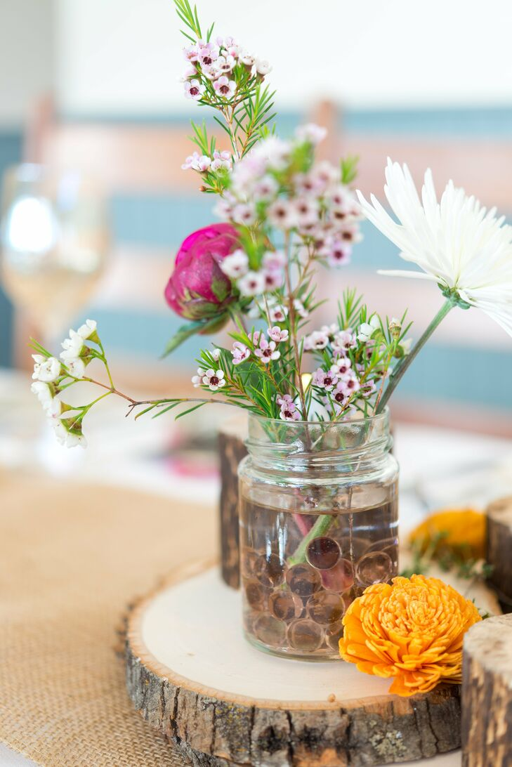 Simple bunches of white and pink flowers filled miniature mason jars at the center of each table.