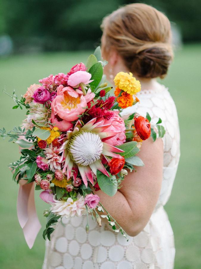 bride holding bright protea bouquet