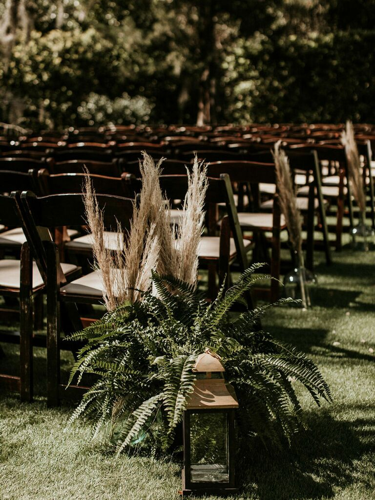 Cottagecore wedding decorations with greenery sprigs and gold lantern