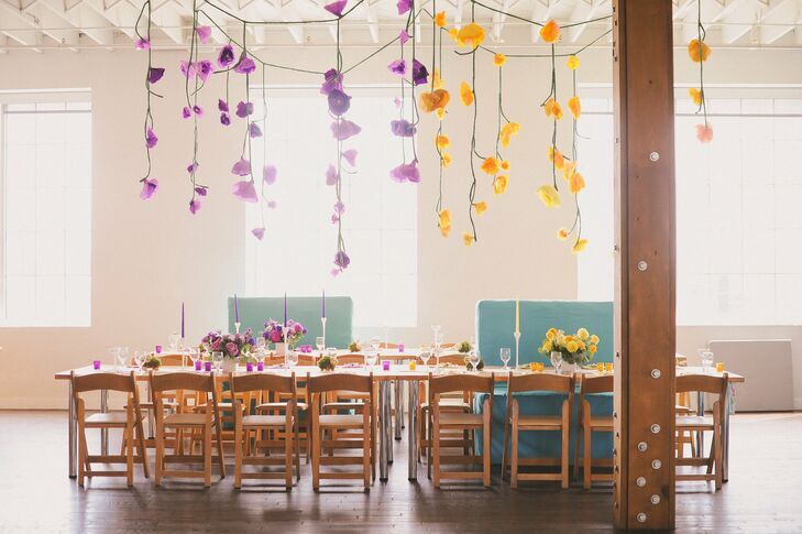 The couple hung colorful handcrafted paper flowers wherever they could, and color-coordinated the blooms with the reception table decor.