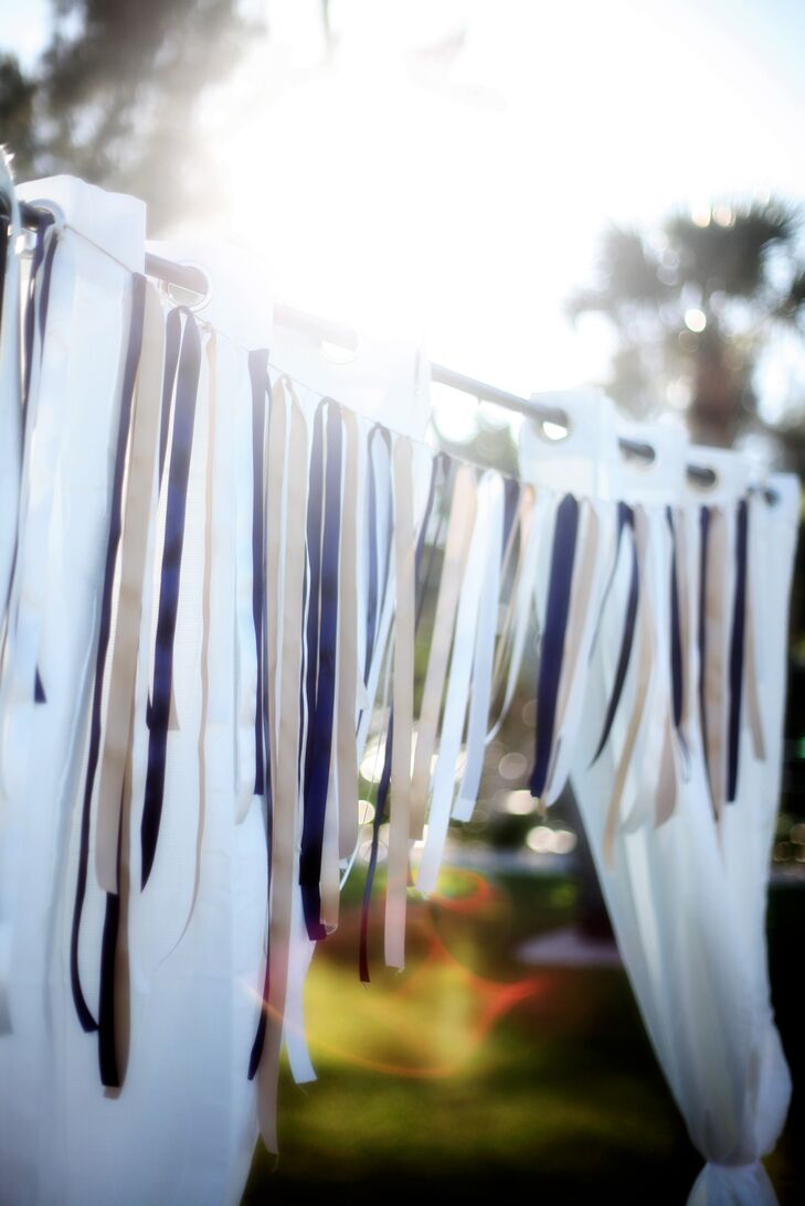 The white draped wedding arch was decorated with black, white and gold streamers.