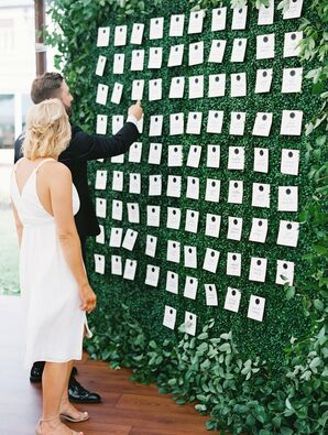Couple Picking Up Escort Cards from Boxwood Display