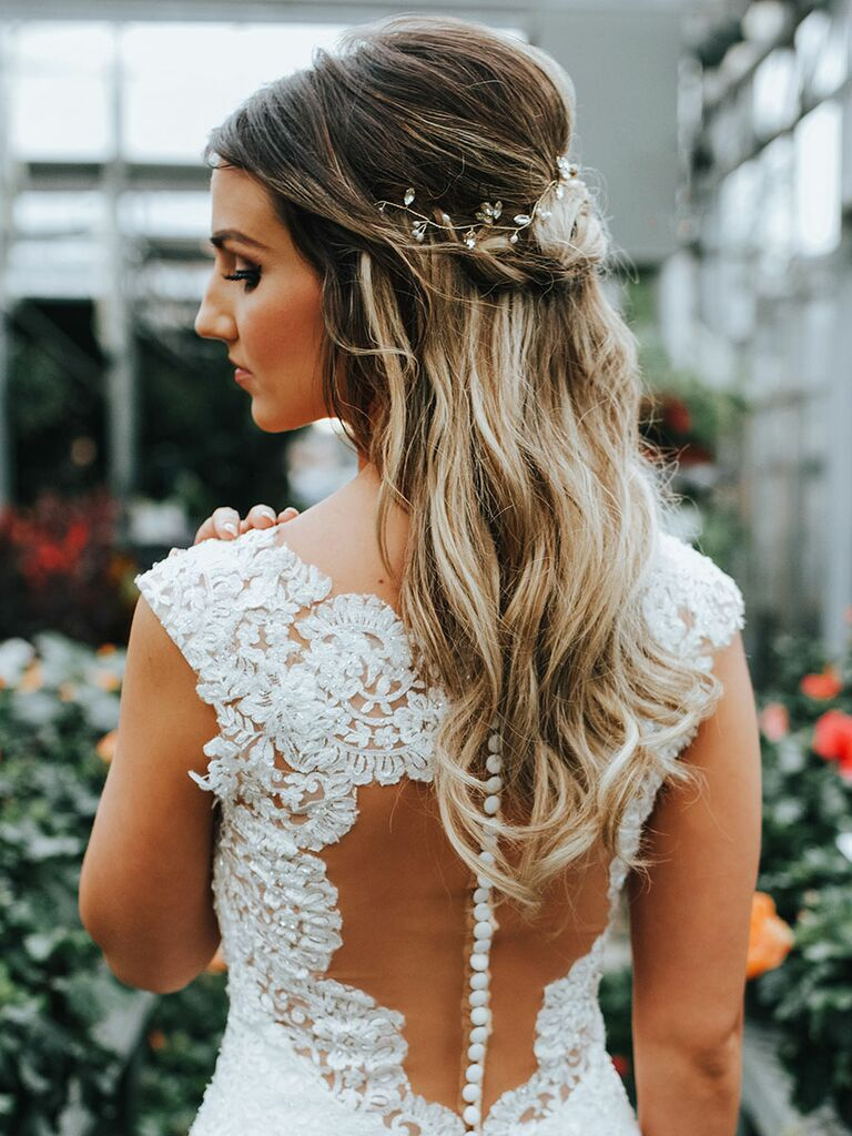Bride shows off wavy hairstyle with metallic accessories.