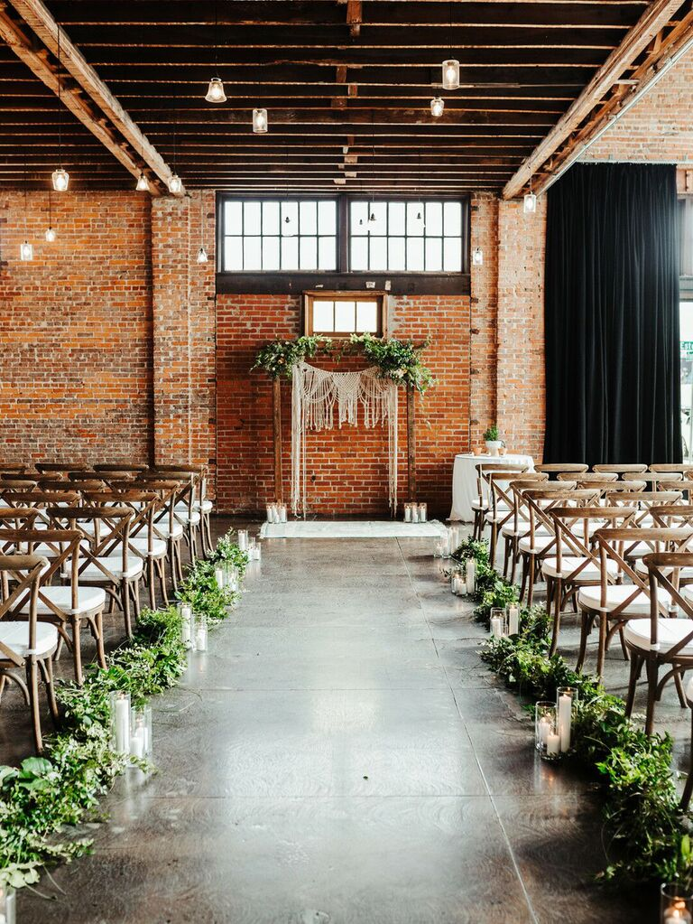 Modern industrial wedding ceremony. with greenery arrangements