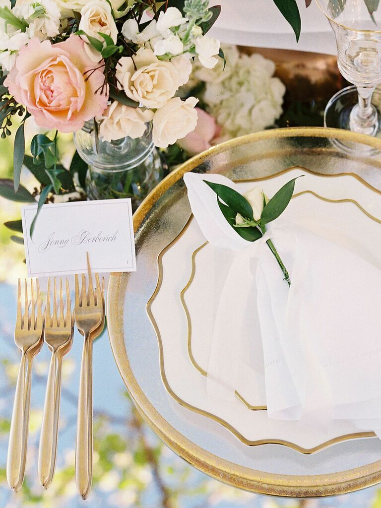 White and gold mismatched china plates on wedding reception tables
