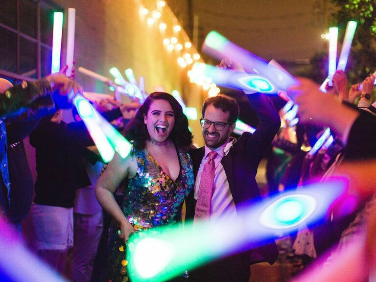 Bride and groom waving light sabers at '90s-inspired wedding