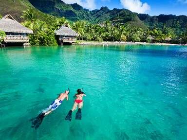 Couple snorkeling in water over coral reef on honeymoon