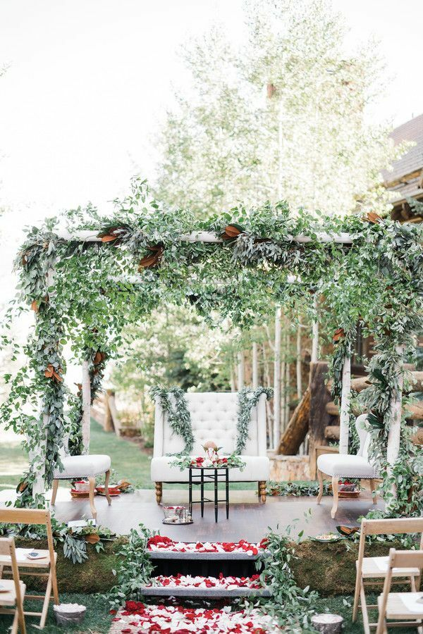 Greenery covered mandap with upholstered chair underneath