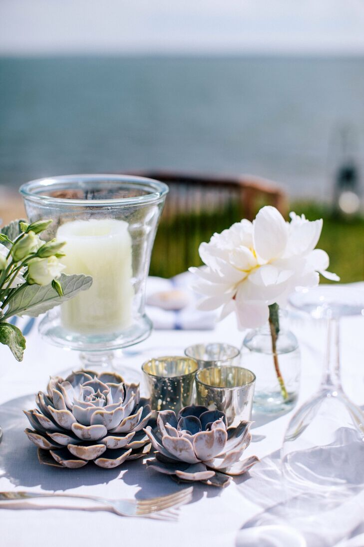 Because the couple didn't want much color in their reception, the centerpieces were made up of white flowers and linens, plus silver elements like tea candles.